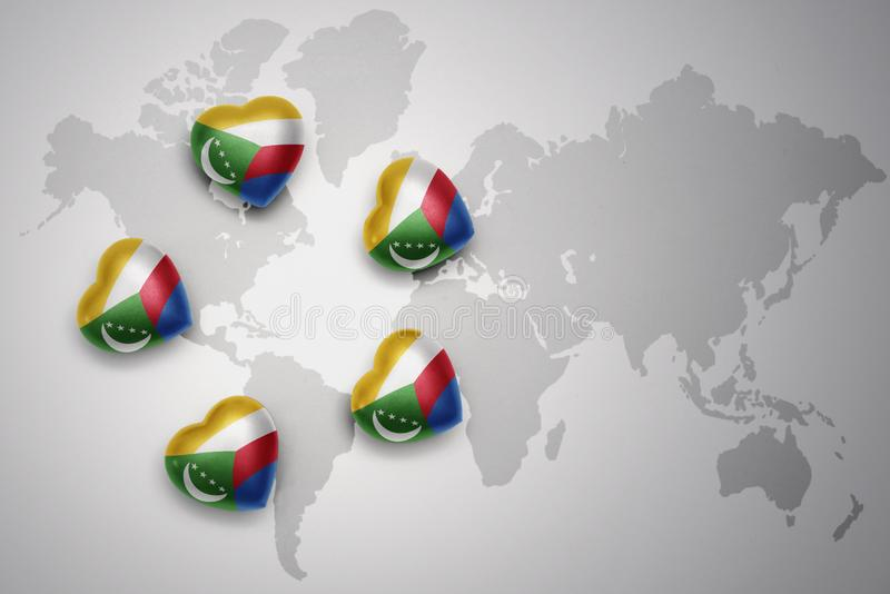 Five hearts with national flag of comoros on a world map background. royalty free illustration