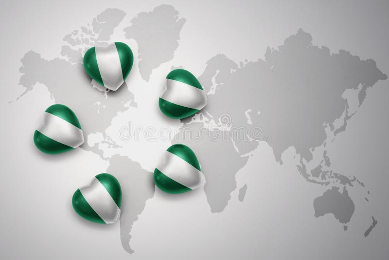 five hearts with national flag of nigeria on a world map background. vector illustration