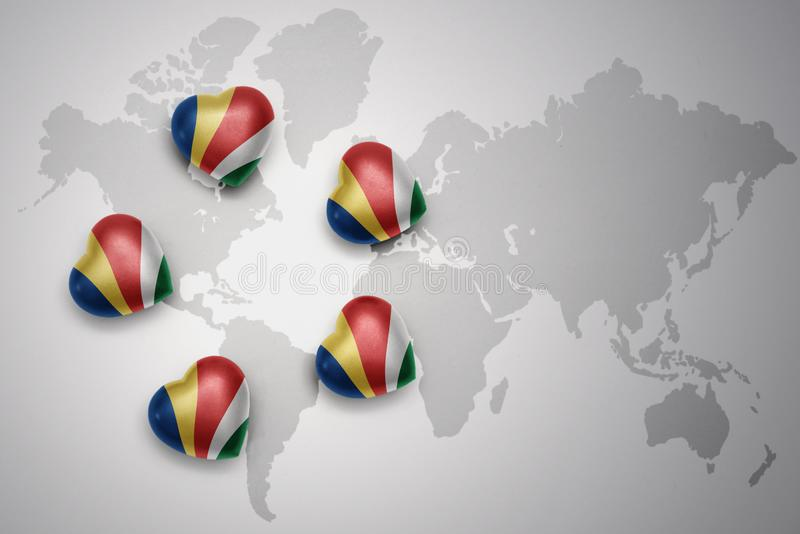 Five hearts with national flag of seychelles on a world map background. stock illustration
