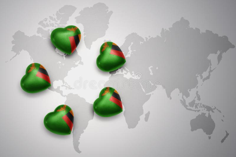 Five hearts with national flag of zambia on a world map background. vector illustration