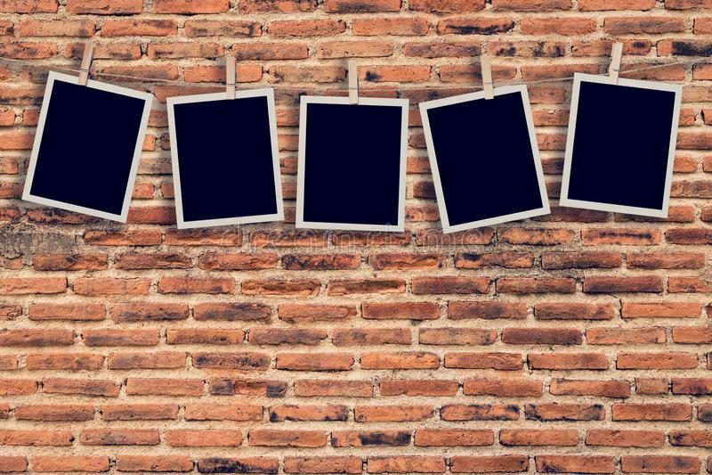 Five instant photo hanging on old brick wall background and text stock images