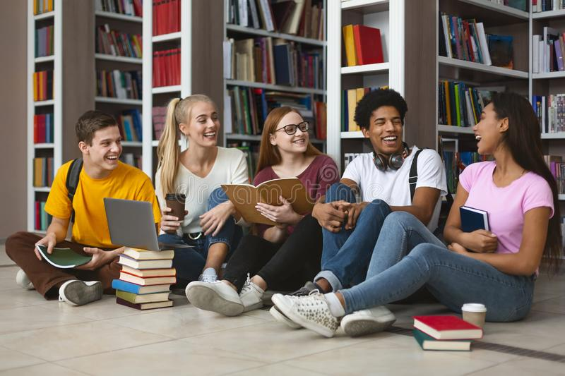 Five international students laughing at university library stock photos