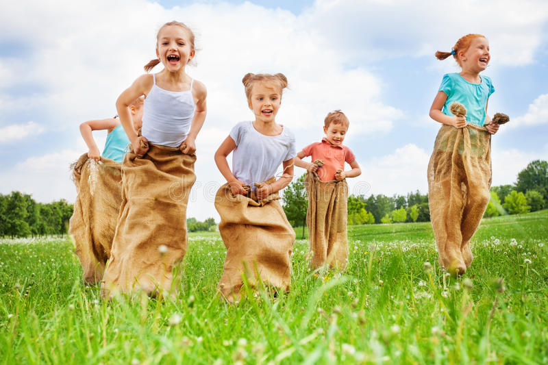 Five kids jump in sacks. On a dandelion meadow on summer hot day