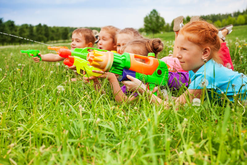 Five kids play with water guns. Laying on a meadow royalty free stock photo