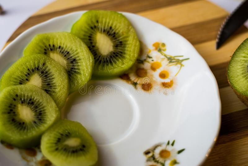 Five kiwi fruit slices on a white table stock image