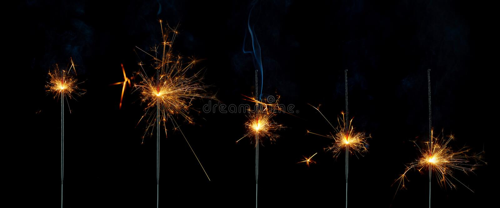 Five lighted sparklers at different stages of burning on a black background. Isolated image. Birthday inscription made of luminous and sparkling Bengali letters royalty free stock photo