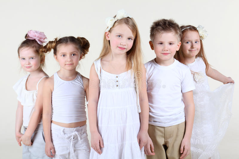 Five little children stand and look at camera