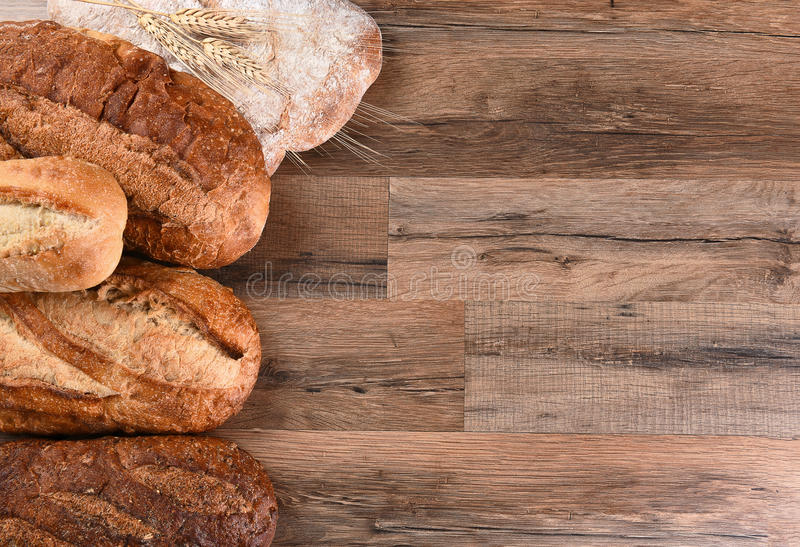 Five Loaves of Bread. Five different loaves of bread on a wood table with copy space. Horizontal format stock photo