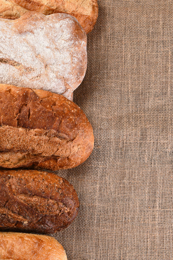 Five Loaves of Bread. Five different loaves of bread on a wood table with copy space. Vertical format royalty free stock image