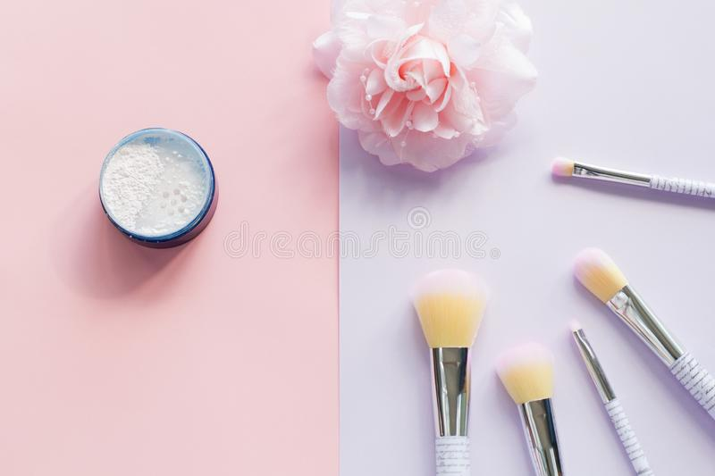 Five makeup brushes with lettering on the handle and mineral powder in a blue jar, bobby pin stock image
