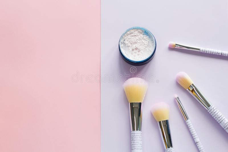 Five makeup brushes with lettering on the handle and mineral powder stock images