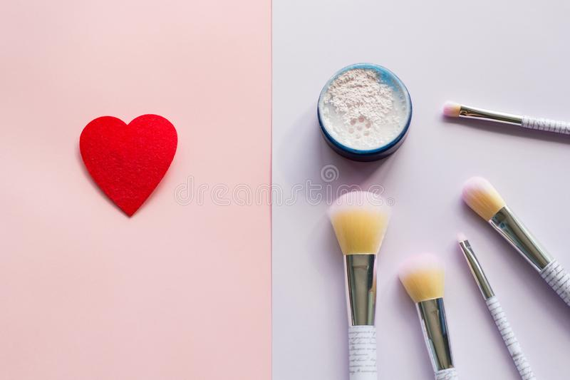 Five makeup brushes with lettering on the handle and mineral powder in a blue jar, red felt brooch stock photography
