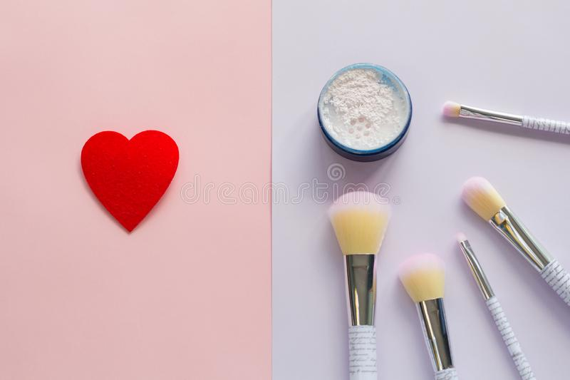 Five makeup brushes with lettering on the handle and mineral powder in a blue jar, red felt brooch in the form of a heart stock photo