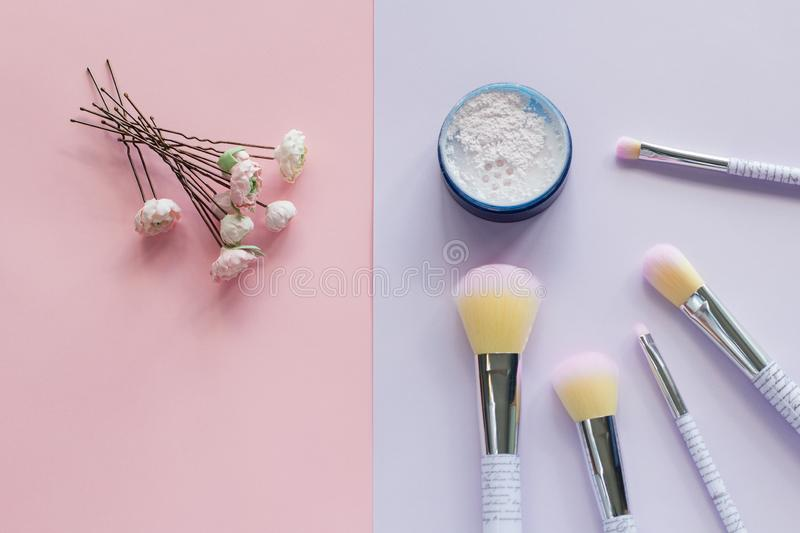 Five makeup brushes with lettering on the handle and mineral powder in a blue jar, wedding hairpins royalty free stock photos