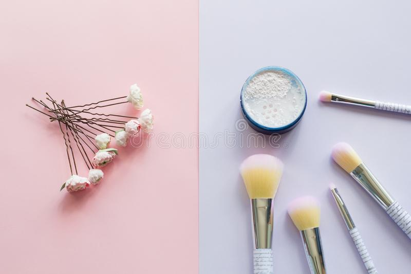 Five makeup brushes with lettering on the handle and mineral powder in a blue jar, wedding hairpins royalty free stock images