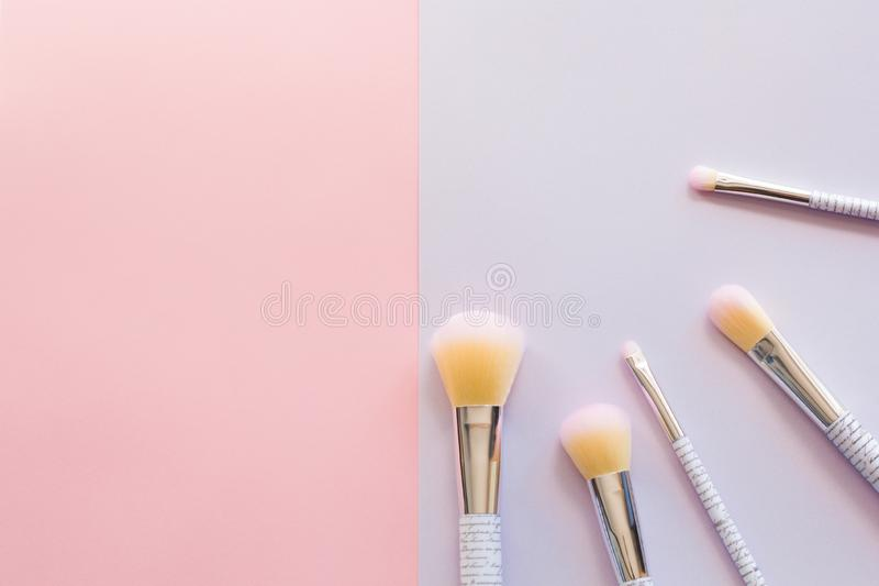 Five makeup brushes with lettering on the handle on pink and purple background. royalty free stock photo