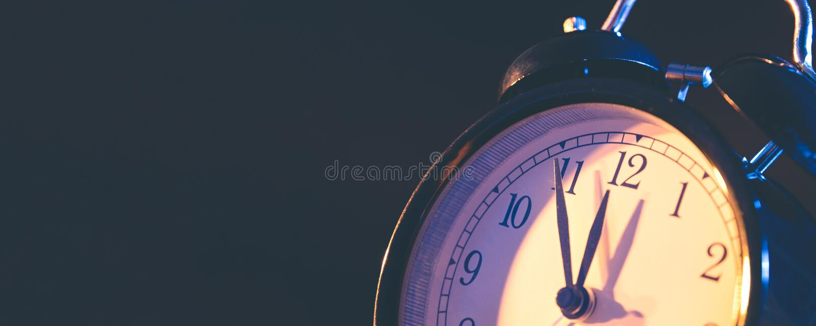 Five minutes to midnight on retro analog clock. Five minutes to midnight. Changing the clocks, time adjustment, daylight savings or new year concept on retro stock photography