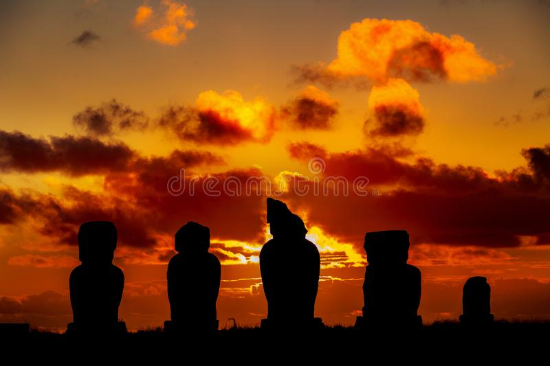 Five moais at Easter Island against orange and red sunset. Five moais at Easter Island against dramatic orange and red sunset royalty free stock image