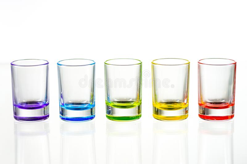 Five multicolored empty shot glasses placed symmetrically on a w royalty free stock images