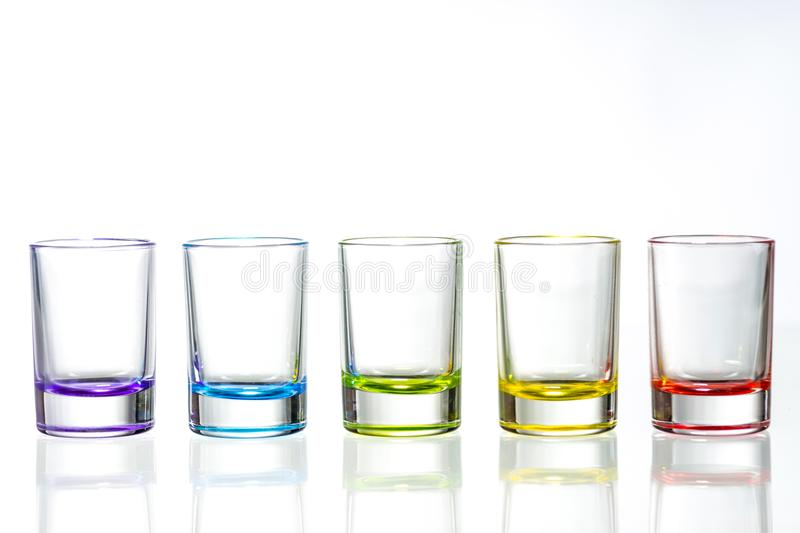 Five multicolored empty shot glasses placed symmetrically on a w stock photo