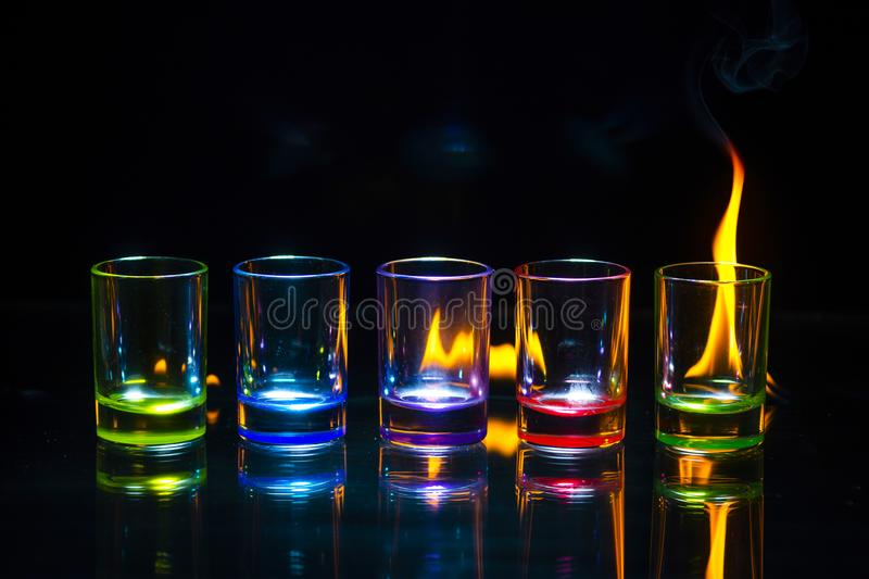 Five multicolored empty shot glasses reflected on the glass surf stock photo