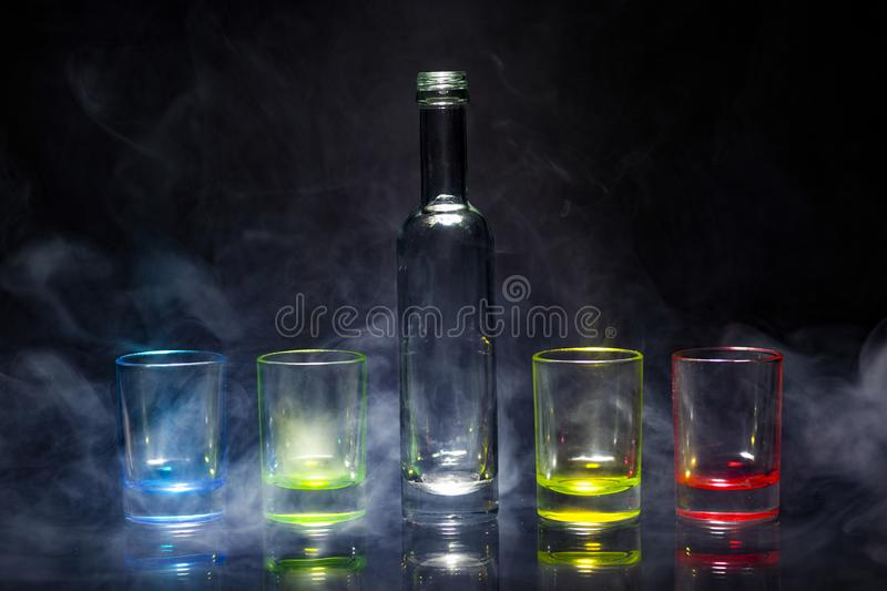 Five multicolored empty shot glasses and small bottle placed symmetrically on a black background in a theatrical smoke royalty free stock images