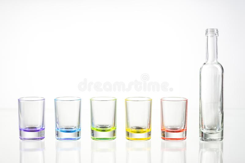 Five multicolored empty shot glasses and small bottle placed unsymmetrically on a white background. stock images