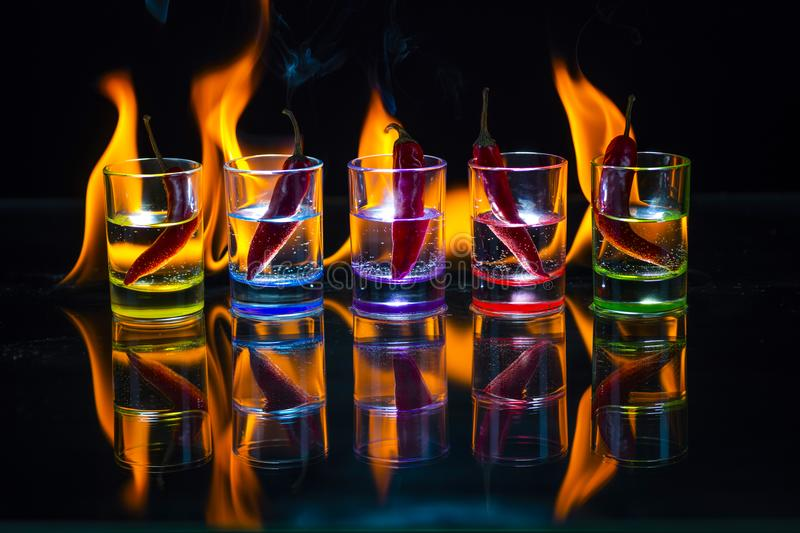 Five multicolored shot glasses full of drink and with the red ch royalty free stock image