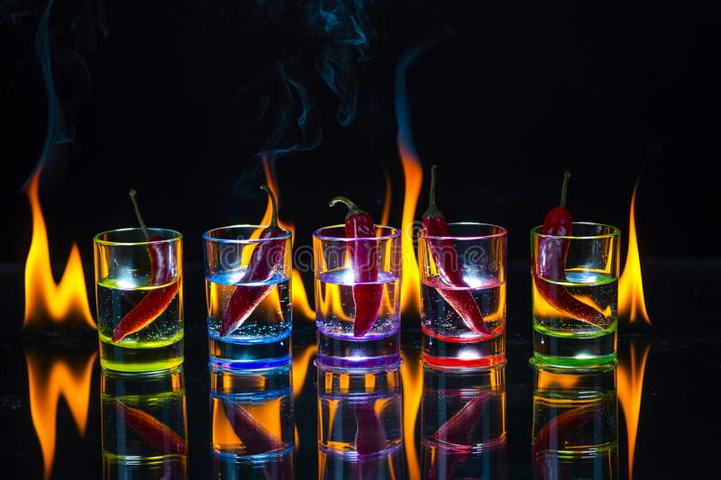 Five multicolored shot glasses full of drink and with the red ch stock image