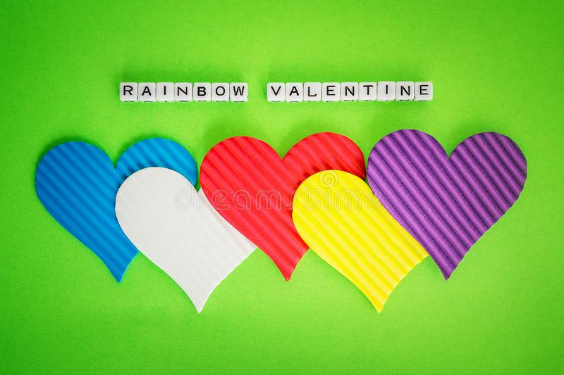 Five multicolored valentine hearts and the inscription Rainbow Valentine made of white alfphabet cubeson a green background stock photo