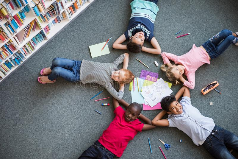 Happy children lying on floor royalty free stock photography