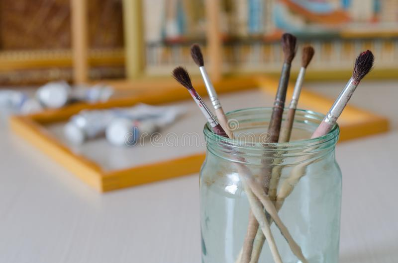 Five paintbrushes in a glass jar. Picture frames, paint stock photo