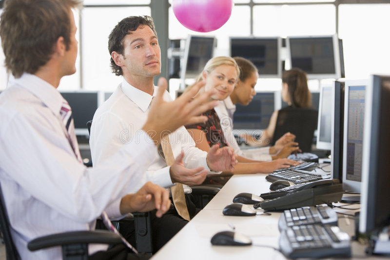 Five people in an office throwing a ball around stock images