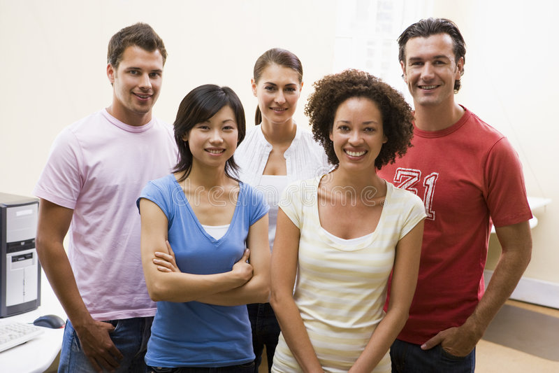Five people standing in computer room smiling royalty free stock images