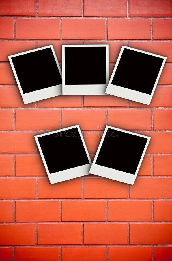 Five photo frame on brick wall