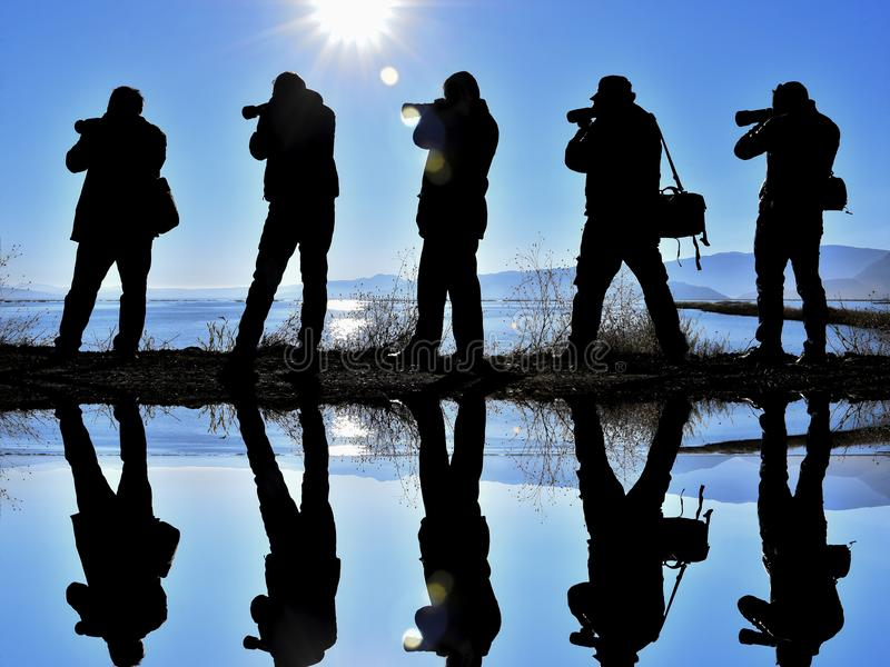Five photographers beside a lake stock photography