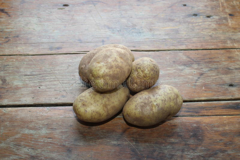 Five potatoes on a distressed wooden table royalty free stock photos