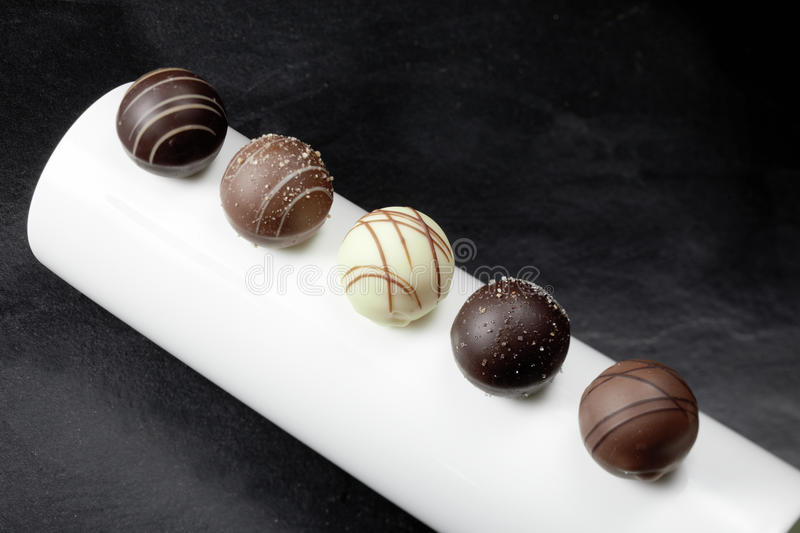Five pralines. Five chocolate pralines in a line stock image