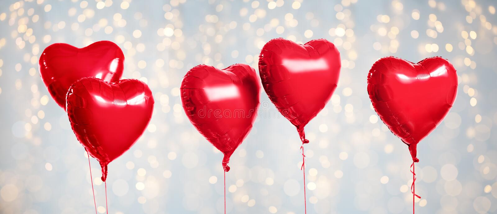 Five red heart shaped helium balloons on white. Holidays, valentines day and party decoration concept - five metallic foil red helium heart shaped balloons over royalty free stock image