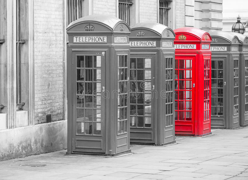 Five Red London Telephone boxes in black and white with one red phone booth royalty free stock images