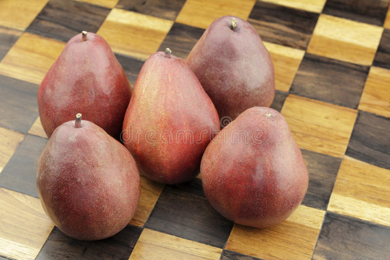 Five Red Pears on a Wooden Chessboard. Five organic red pears close-up on a solid wooden inlay chess board background. Several organic red pears grouped together royalty free stock image