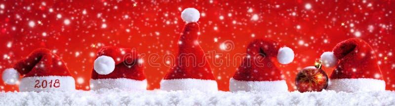 Happy new year 2018 santa hats and snowfall. royalty free stock photography