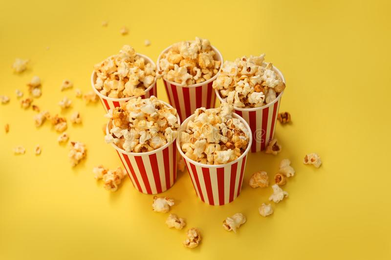 Five red-and-white paper cups with popcorn on a yellow background, several pieces are scattered nearby, copy space royalty free stock photography
