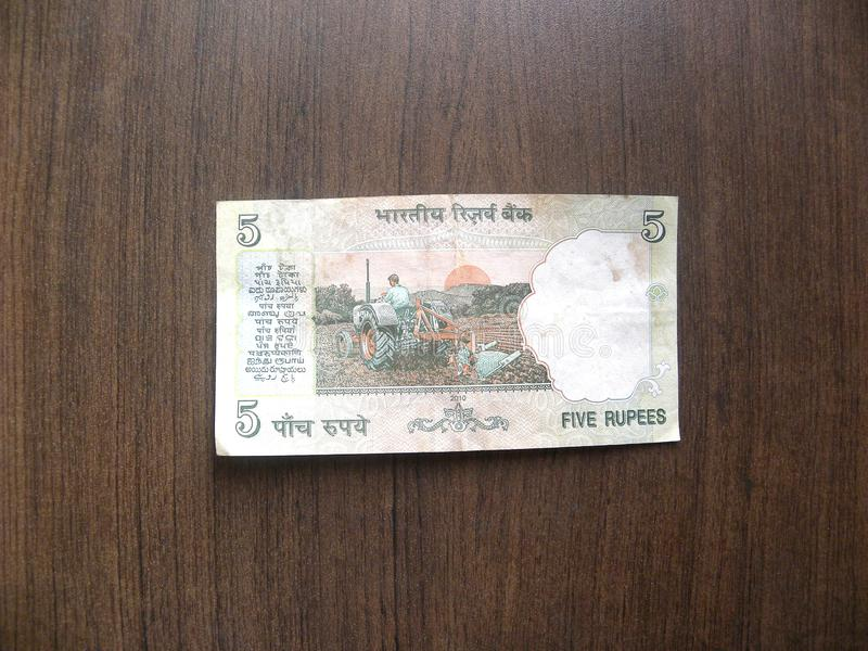 Five rupees India note. Reverse of green color 5 rupees India banknote with Indian Man Ploughing Field using tractor portrait kept on wooden table royalty free stock photos
