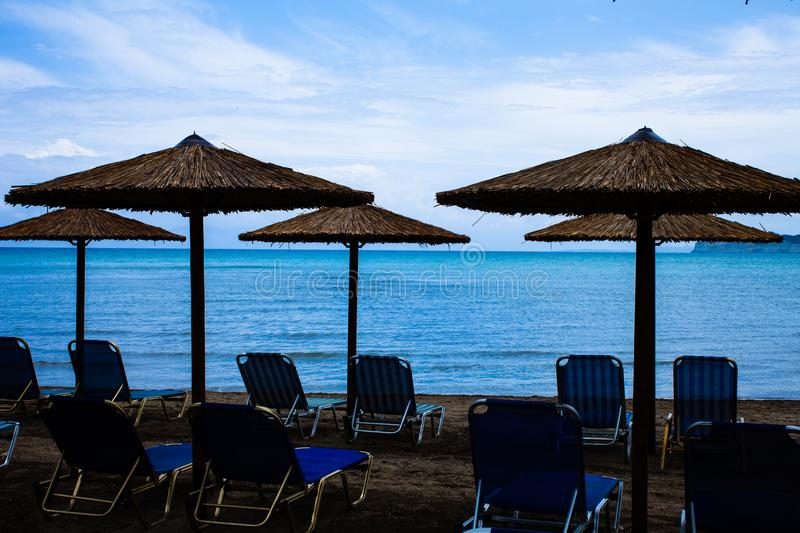 Five Rustic Palapa Umbrellas located at the shoreline of the mediterranean sea with Folding Blue Chairs over the Sand, Beautiful V stock images