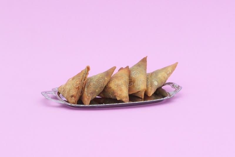 Five samosas on a sliver platter. Five freshly fried samosas on a silver platter against a pink background stock image