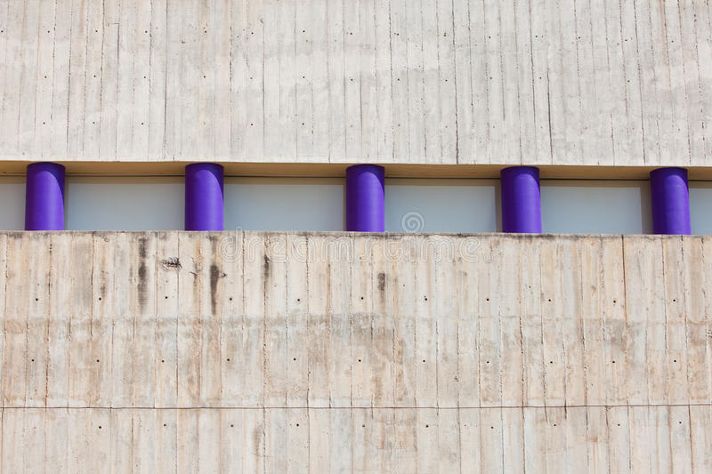 Five short purple pillars in concrete wall stock photography