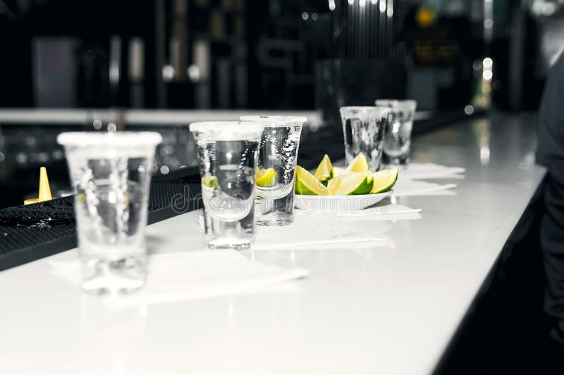 Five shots of tequila with lime and salt on a white bar counter against a bar background stock photos