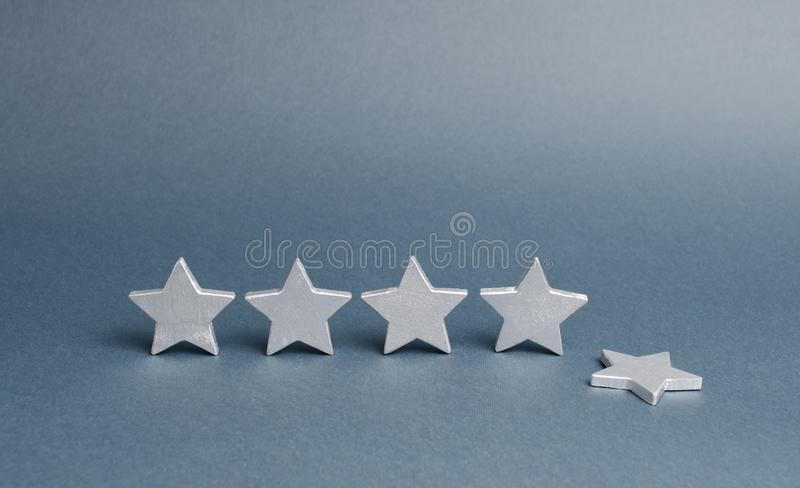 Five silver stars, one star fell. Loss of rating and level, reducing prestige and reputation. Rating and status of the restaurant. Or hotel. Prestige and a good royalty free stock photos