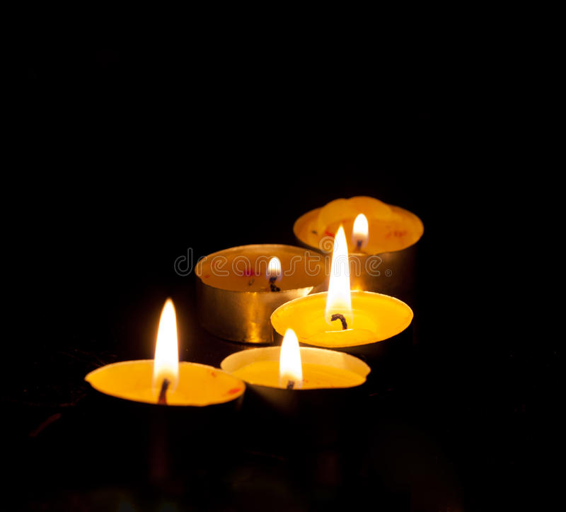 Five small burning candles stock image